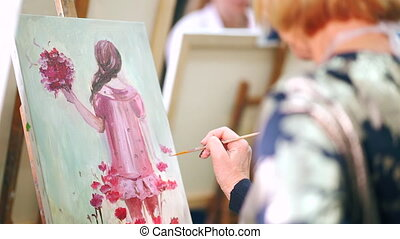 Woman's artist hands painting picture with oil paints on...