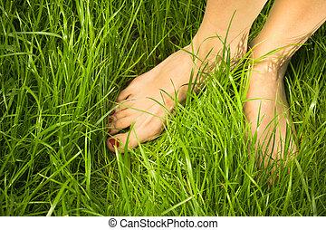 Woman's bare feet in green