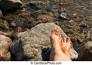 Woman's bare feet near the sea on rock