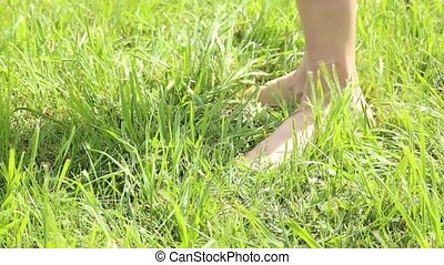 woman's bare feet walking over green grass field, she throwing shoes on grass