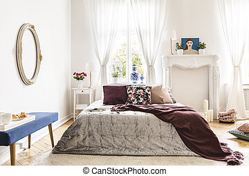 Woman's bedroom interior with vintage accents. A bed dressed in a silver throw, a brown blanket and many pillows against a wall with an ornamented fireplace portal and a sunny window. Real photo