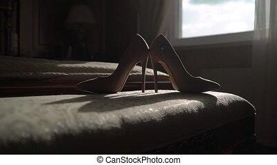 Woman's beige shoes in bedroom oh high heels
