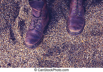 Woman's boots on pebble beach