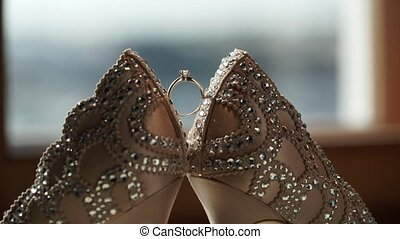Woman's bridal luxury shoes and wedding proposal ring at sun...
