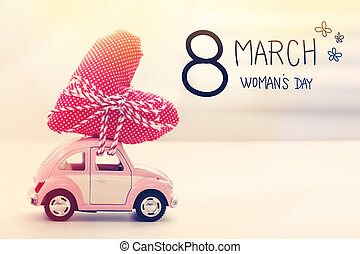 Womans Day message with miniature pink car carrying a heart ...