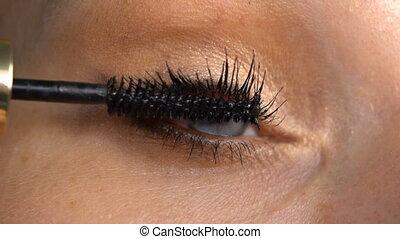 Woman's eye applying makeup