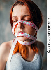 Womans face tied with measuring tape, weight loss