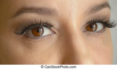 Woman's face with long false lashes opens her brown eyes and...