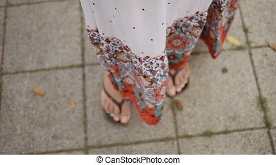 Woman's feet in flip-flops under fluttering from the wind colorful skirt