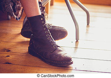 Woman's feet in leather boots on wooden floor