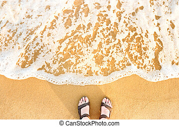 Woman's feet in sandals on a beach sand