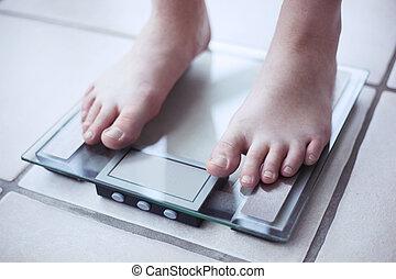 Woman's feet on bathroom scale.