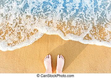 Woman's feet on yellow beach sand