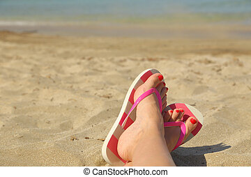 Womans feet with flip flops on the sand