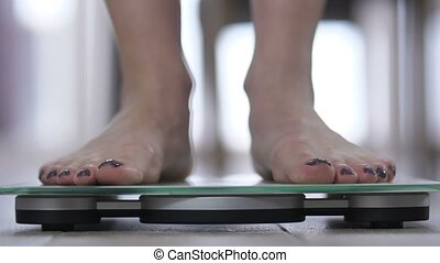 Woman's feets standing on body weight scales