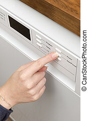 Woman's Finger Pressing a Button on a Home Dishwasher Appliance