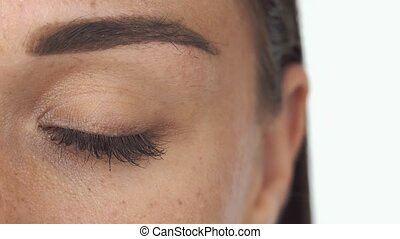 Woman's green eye with a brow and freckles on white background