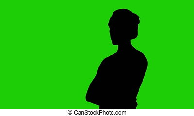 Woman's half turned silhouette with arms crossed on green background