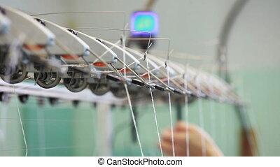 Woman's hand adjusts thread on loom
