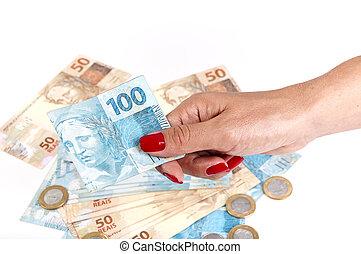 Woman's hand holding Brazilian money on white background