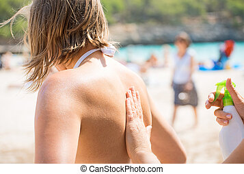 Woman's hand applying suntan cream on female back.