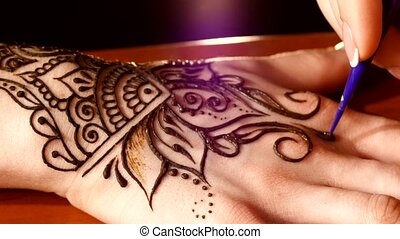 Womans hand being decorated with henna tattoo, mehendi, on...