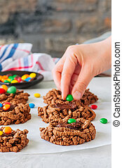 Woman's hand decorated chocolate bird's nest cookies with ganache and colorful candies. White background.