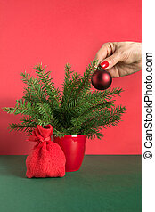 Womans hand decorates small Christmas tree with red balls.