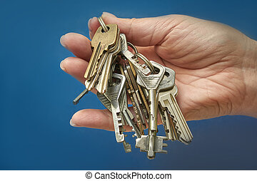 Woman's hand holding a bunch of keys on a blue background
