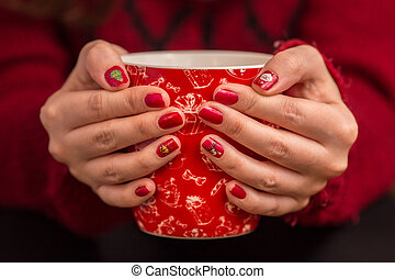 Woman's hand holding a red cup of coffee. With a beautiful winter manicure.