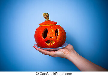 Woman's hand holding a scary halloween pumpkin