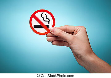 woman's hand holding a symbol - no smoking. Against blue...
