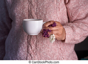 Woman's hand holding a white cup of coffee. With a beautiful lilac flowers. Drink, fashion, morning