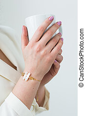 Woman's hand holding a white cup of coffee. With a beautiful manicure close-up. Drink, fashion, morning
