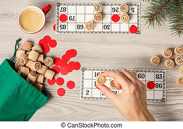 Woman's hand holding a wooden barrel for a game in lotto