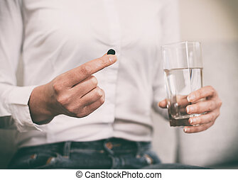 Woman's hand holding activated carbon pills.