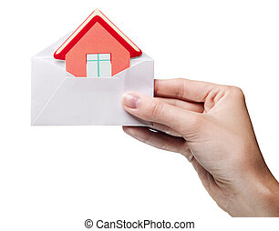 woman's hand holding an envelope with a sign of the house...