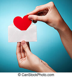 woman's hand holding an envelope with a sign of the heart...