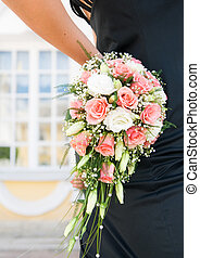 Woman's hand holding beautiful bouquet of roses