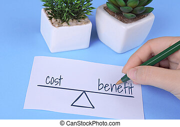 """Woman's hand holding card with words """"cost vs. benefit"""""""
