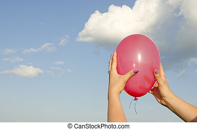 womans hand holding red balloon