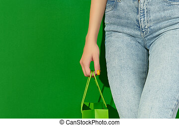 Womans hand holding shopping bag on green background. Shopping sale concept