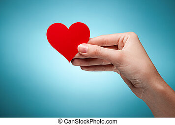 woman's hand holding symbol - red heart. Against blue...