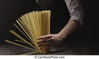Woman's hand holds a bunch of italian pasta on a dark...