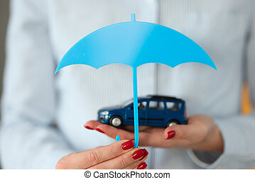 Woman's hand holds car and an umbrella