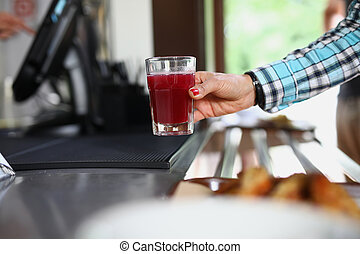 Woman's hand holds glass in cafe with red liquid similar to ...