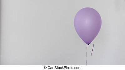 Womans hand holds purple balloon white background isolated