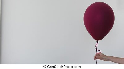 Womans hand holds purple balloon white background - Womans...