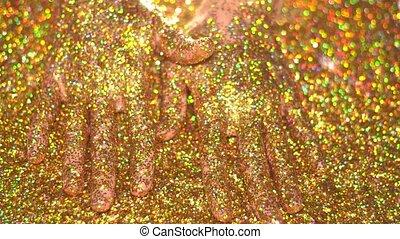 Woman's hand in golden glitter sparkles