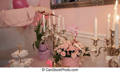 Woman's hand lights wax candles on table in living room.